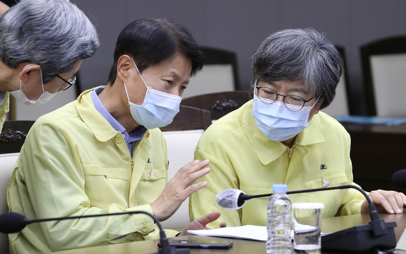Vice Health Minister Kim Kang-lip (L) speaks to Jung Eun-Kyeong, Director of the Korea Centers for Disease Control and Prevention, during a coronavirus meeting at the government complex in Sejong on August 14, 2020.