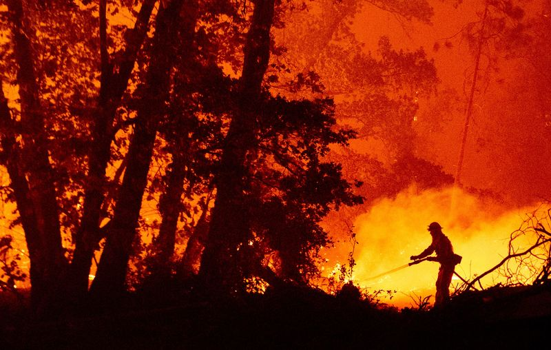 A firefighter douses flames as the Creek Fire pushes near homes in Madera County, California, on Sept. 7, 2020.