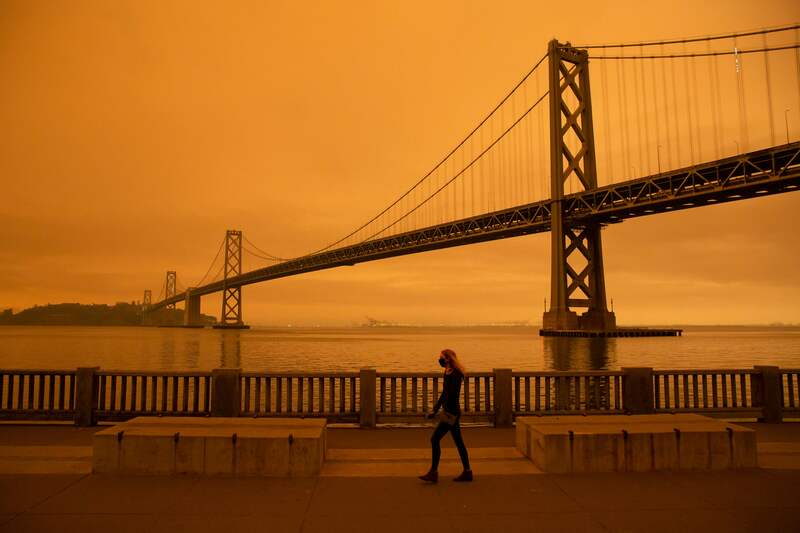 A woman walks along a waterfront area under an orange smoke-filled sky in San Francisco, California on Sept. 9, 2020.