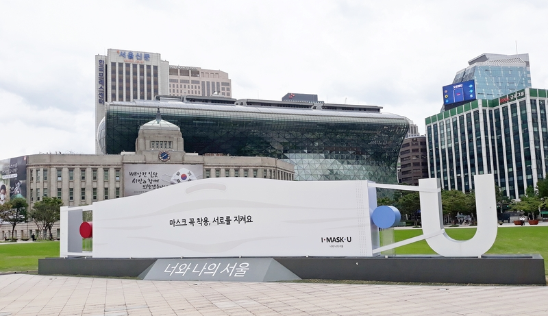 A large mask-shaped signboard promoting the use of protective face coverings sits outside Seoul City Hall.