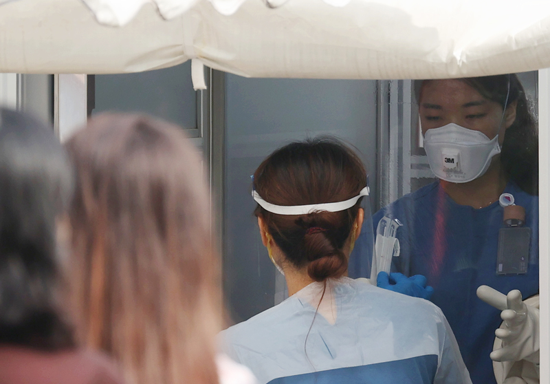 A medical worker helps people lined up outside a coronavirus screening facility at the National Medical Center in Seoul on Sept. 15, 2020.
