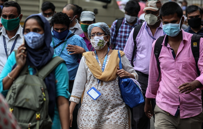 Indian office-goers wearing protective face masks walk on the street in Mumbai, India, which has the second highest caseload of COVID-19 in world.