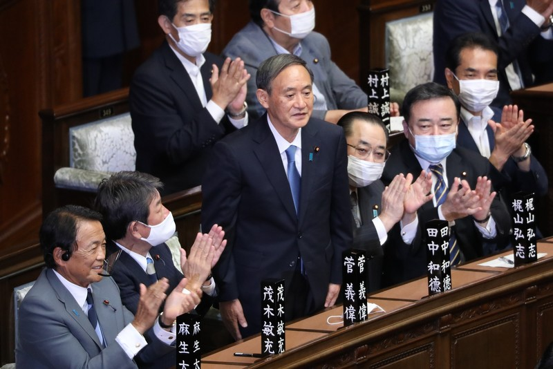 Yoshihide Suga (C) stands after being elected as Japan's new prime minister in Tokyo on Sept. 16, 2020.