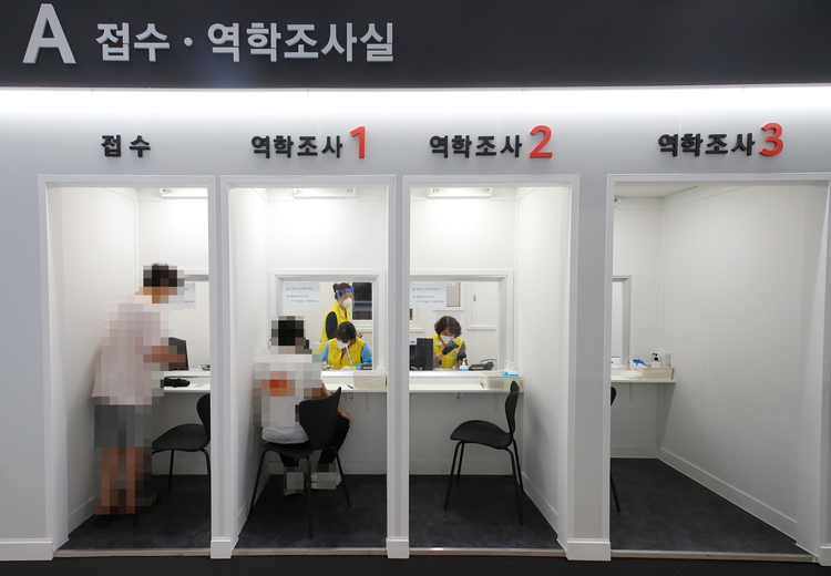 Medical workers help people get tested for COVID-19 at an untact screening center in Seoul's southern Seocho District.