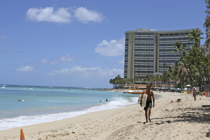 A surfer walks on a sparsely populated Waikiki Beach in Honolulu, Hawaii.