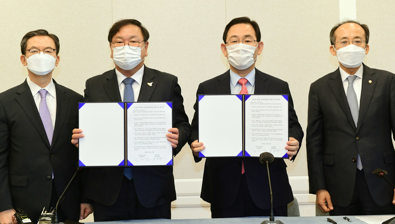 The floor leaders of the ruling Democratic Party and main opposition People Power Party pose for a picture after signing an agreement on Sept. 22, 2020, on the fourth extra budget drawn up this year to fend off the economic impact of the coronavirus pandemic.