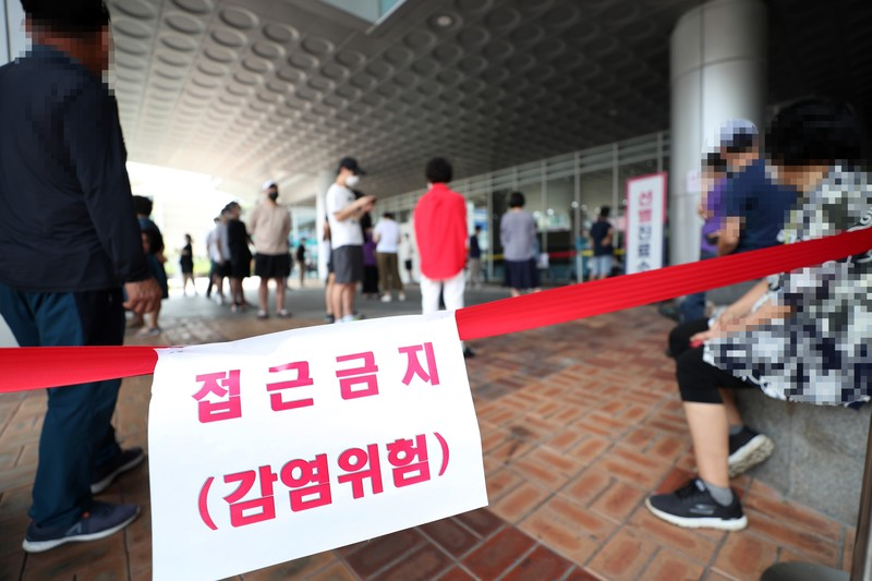 People stand in line to get tested at a COVID-19 screening facility that has been cordoned off by red tape and a sign warning visitors of the risk of infection.