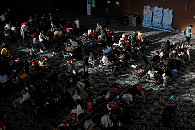 Travelers wearing face masks wait at Beijing Daxing International Airport amid the global outbreak of COVID-19.