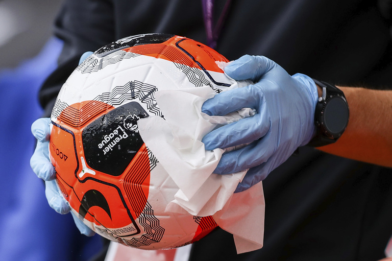 An English Premier League official disinfects a ball before a game.