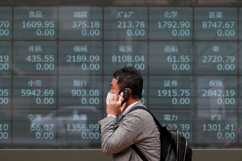 A man wearing a mask walks in front of a stock quotation board with blank prices after the Tokyo Stock Exchange temporarily suspended all trading due to a glitch in Tokyo, Japan. on Oct. 1, 2020.