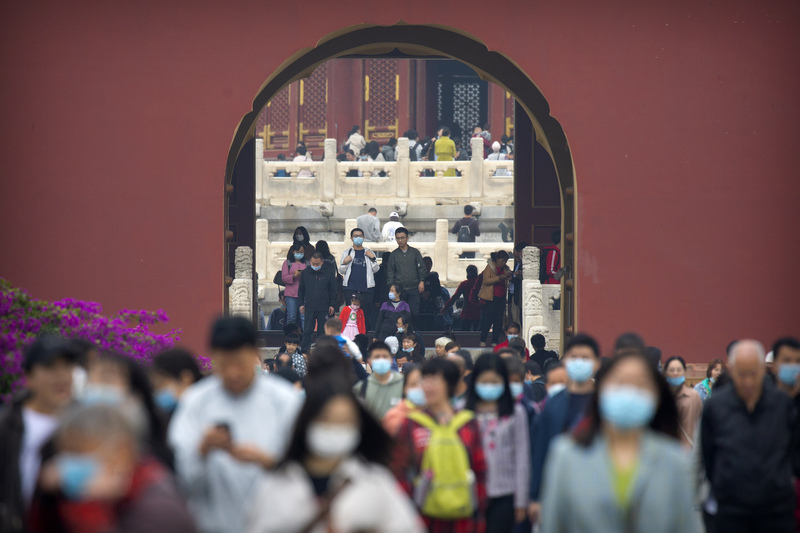 Visitors wearing face masks walk around the Temple of Heaven in Beijing on Oct. 1, 2020, as millions of people across China observe the week-long National Day holiday.