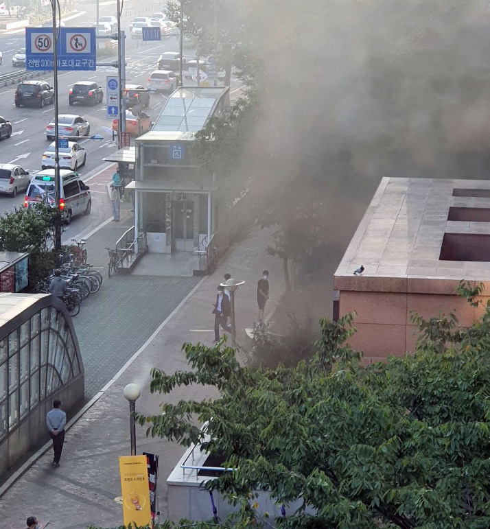 Smoke is seen coming out of a residential complex connected to Mapo Station after a fire is reported Tuesday afternoon.