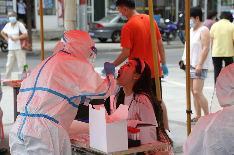 A medical worker in China collects a swab sample from a woman to test for COVID-19.