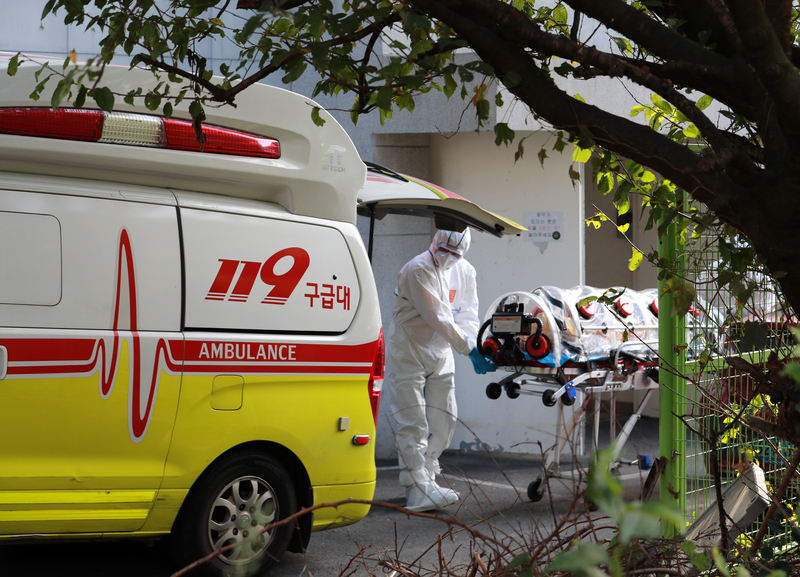 Emergency medical workers transfer a coronavirus patient from a convalescent hopital in Busan on Oct. 14, 2020. More than 50 elderly patients and staff at the facility have tested positive for COVID-19.