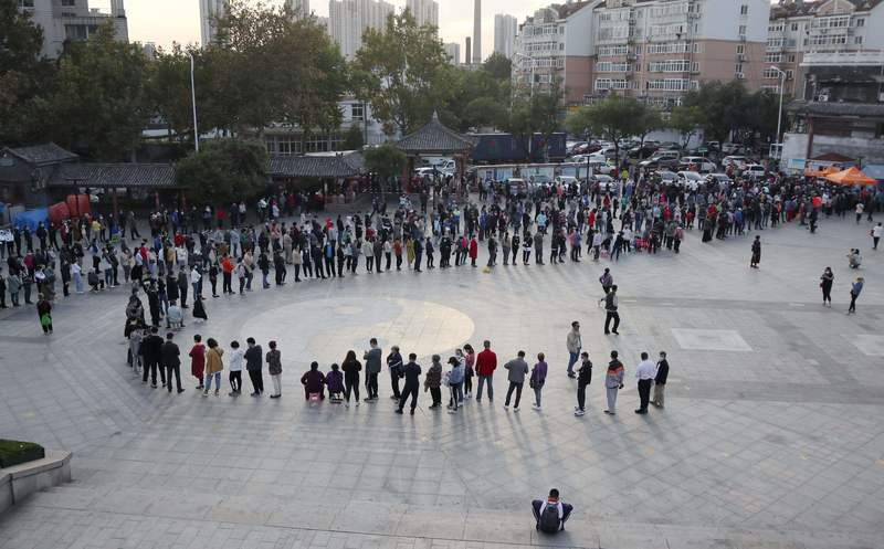 People in the city of Qindao in China's Shandong Province line up to get tested for COVID-19 after an outbreak was reported at a local hospital.