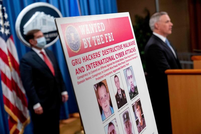 A poster showing six wanted Russian military intelligence officers is displayed as U.S. Attorney for the Western District of Pennsylvania Scott Brady speaks at a news conference at the Department of Justice in Washington, D.C., on Oct. 19, 2020.