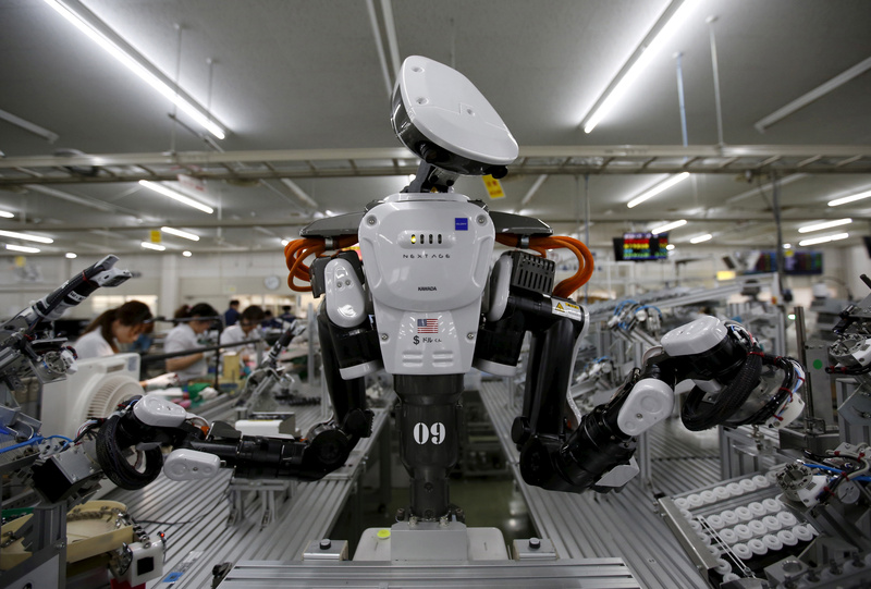 A humanoid robot works side by side with employees in the assembly line at a factory Kazo, Japan.