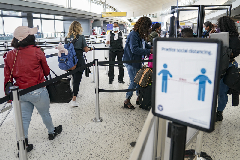 U.S. Transportation Security Administration personnel and travelers observe COVID-19 protocols at John F. Kennedy International Airport in New York on Oct. 20, 2020.