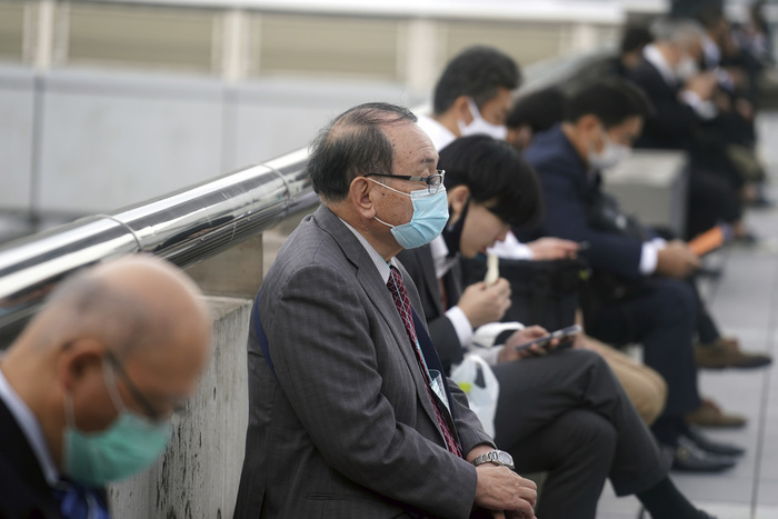 People wearing protective masks to help curb the spread of COVID-19 rest in Chiba, Japan. (Photo: AP-Yonhap News)