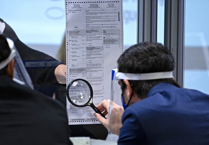 An official at the Miami-Dade Elections Department in Florida inspects a ballot with a magnifier. (Photo: AP-Yonhap News)