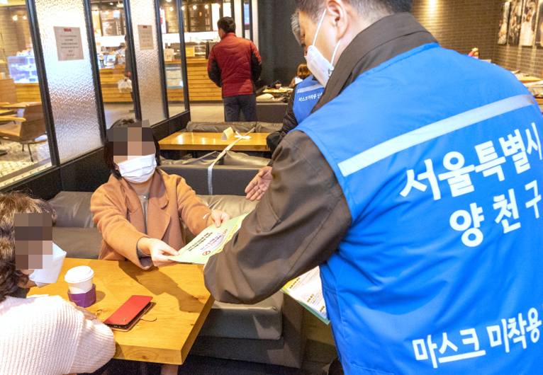 An official from the Yangcheon District Office in Seoul hands out notices to café customers reminding them they can face a fine of up to 100,000 won for failing to properly wear masks on Nov. 13, 2020. (Photo: Yonhap News)