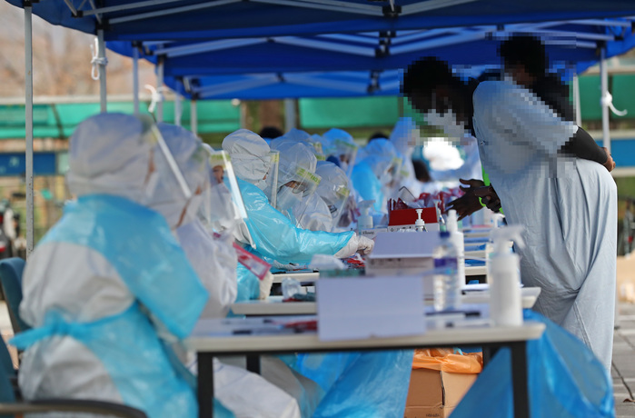 Health workers in protective suits help people seeking virus testing at a makeshift COVID-19 screening site in Asan, South Chungcheong Province, on Nov. 20, 2020. (Photo: Yonhap News)