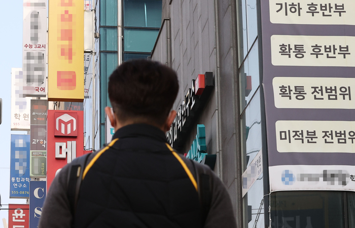 A man walks past buildings packed with academies and cram schools in Seoul. (Photo: Yonhap News)