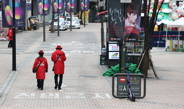 Two tourist information officers walk along an empty street in the normally busy Myeongdong shopping district in Seoul on Nov. 29, 2020. The greater Seoul area remains under Level 2 social distancing amid a surge in coronavirus infections nationwide. (Photo: Yonhap News)