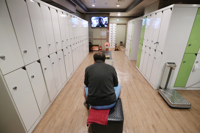 A worker at a sauna facility in Seoul sits in an empty locker room on Nov. 30, 2020. (Photo: Yonhap News)