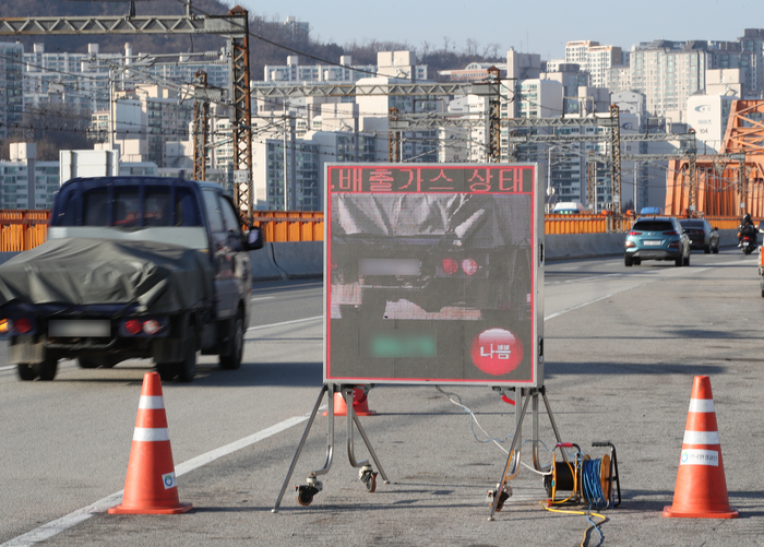 An electronic sign board displays the image of high-polluting vehicles detected on a bridge in Seoul. (Photo: Yonhap News)