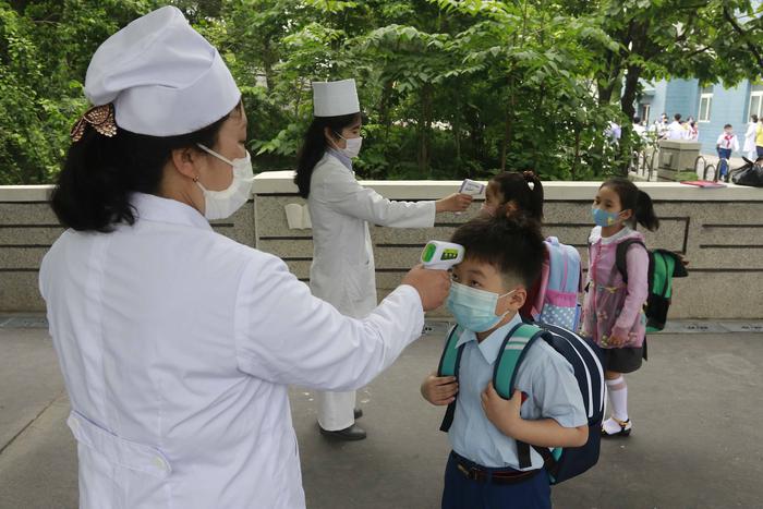 Primary school students have their temperatures checked before entering school in Pyongyang, North Korea. (Photo: AP-Yonhap News)