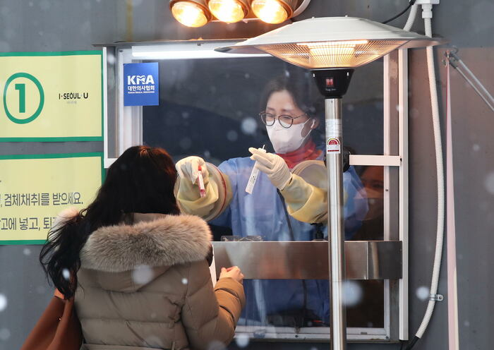 A health worker takes swab samples from a person to screen for COVID-19 at a walk-through testing center near Seoul Plaza amid snowy conditions on Jan. 18, 2021. (Photo: Yonhap News).