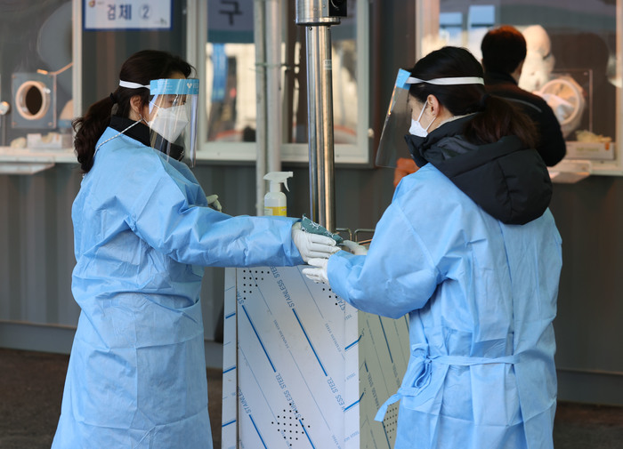 Health workers share heat packs with each other to keep warm amid freezing temperatures as they stand outside a free COVID-19 testing center at Seoul Station on Jan. 19, 2021. (Photo: Yonhap News)