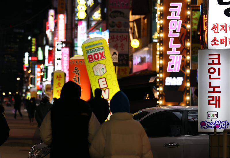 The neon signs of coin-operated singing rooms in Seoul's Songpa District attract passersby on Jan. 18, 2021. (Photo: Yonhap News)