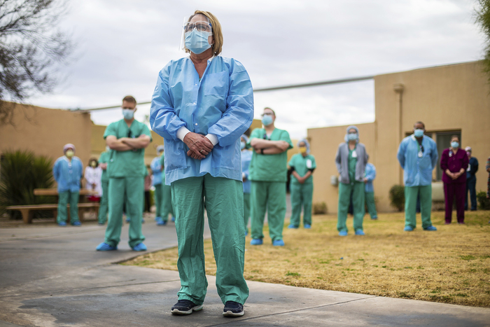 Health workers at Tucson Medical Center stand during a ceremony to remember those who have died of the coronavirus on Jan. 19, 2021, in Tucson, Arizona. (Photo: AP-Yonhap News)