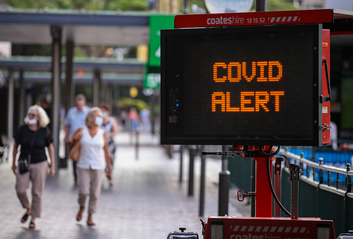 An electronic screen flashes a COVID-19 alert near the Sydney Opera House in Australia. (Photo: Xinhua-Yonhap News)