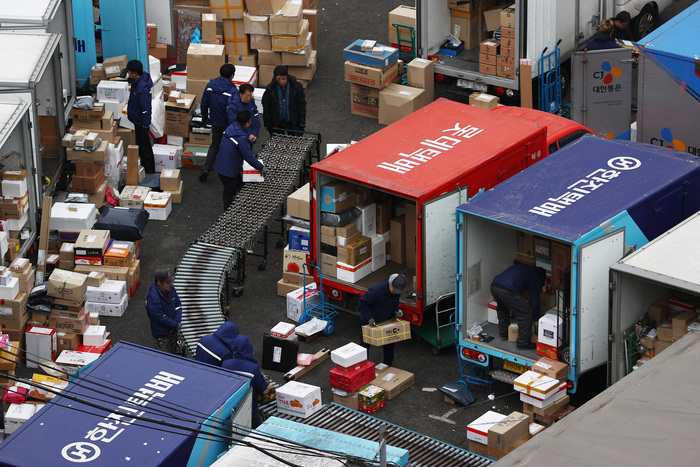 Delivery workers sort through parcels at a distribution center in Seoul on Jan. 21, 2021. (Photo: Yonhap News)