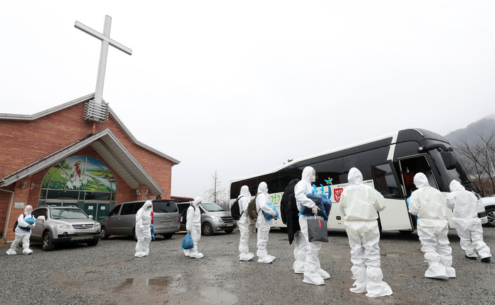 IEM School students infected with COVID-19, wearing protective suits and masks, leave a training facility in Hongcheon County to receive treatment on Jan. 26, 2021. (Photo: Yonhap News)