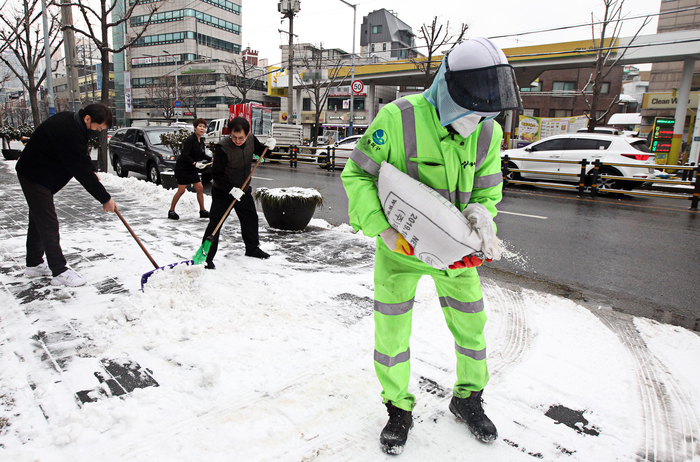 Public workers in Seoul's Dongjak District clear snow from the sidewalks ahead of freezing temperatures forecast to set in late Thursday. (Photo: Yonhap News)