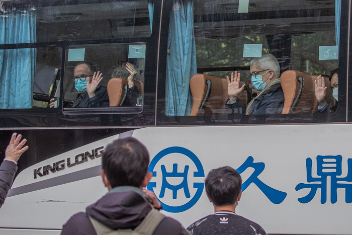 Members of the WHO team wave as they leave the hotel where they quarantined for 14 days in Wuhan, China. (Photo: EPA-Yonhap News)