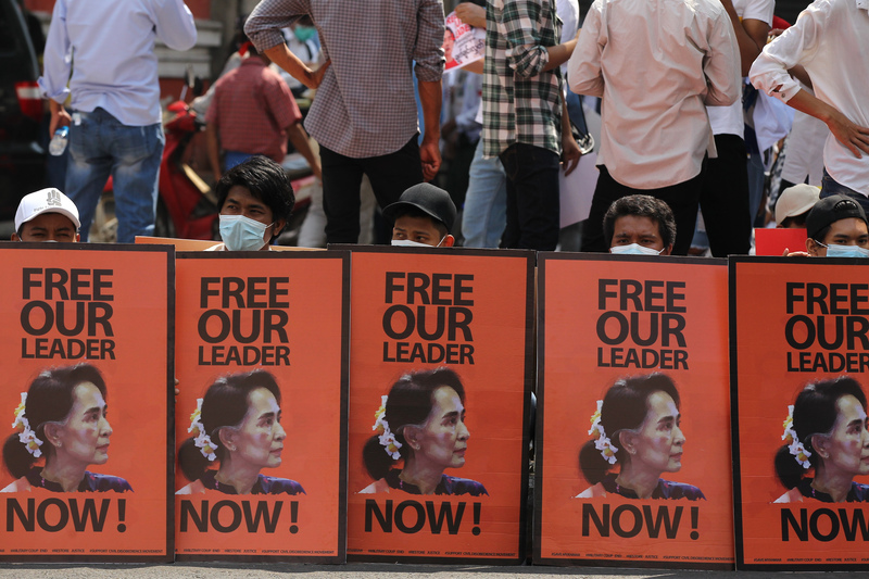 Anti-coup protesters in Myanmar's Yangon sit behind posters with an image of deposed leader Aung San Suu Kyi on Feb. 22, 2021. (Photo: AP-Yonhap News)
