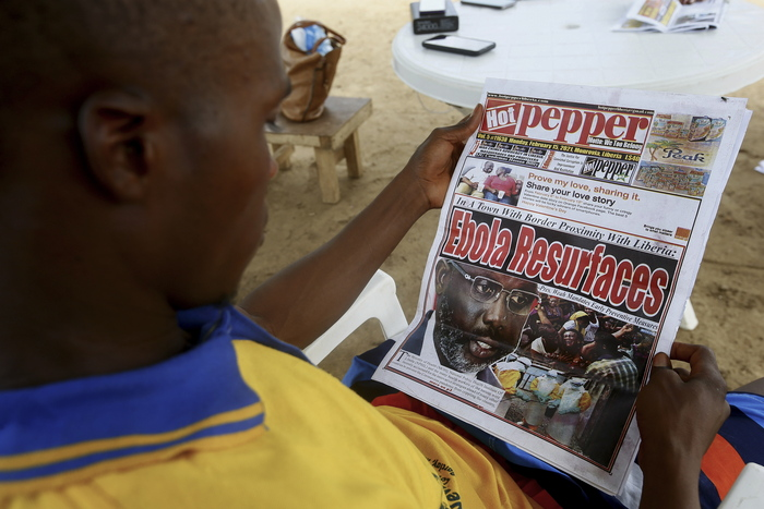 A Liberian man reads a newspaper reporting on the Ebola outbreak in neighbouring Guinea on Feb. 16, 2021. (Photo: EPA-Yonhap News)