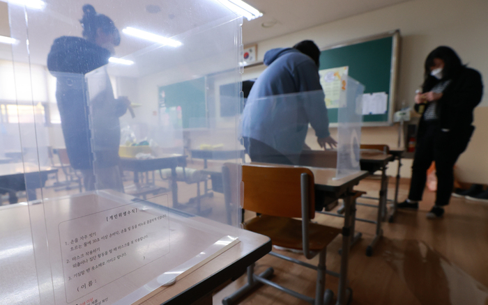 Teachers at Eonnam Elementary School in southern Seoul set up protective plastic shields on classroom desks before the start of the 2021 academic semester. (Photo: Yonhap News)