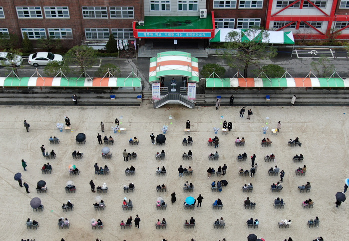 Young students and their parents sit spaced out, in line with social distancing measures, during a welcoming ceremony to kick off the new semester at an elementary school in Daejeon on March 2, 2021. (Photo: Yonhap News)