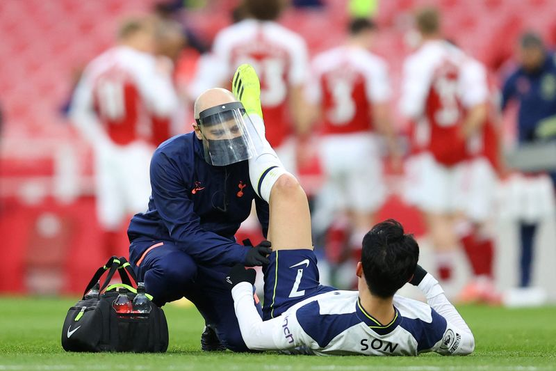 Tottenham Hotspur striker Son Heung-Min (R) is treated for a hamstring injury during a match against Arsenal on March 14, 2021. (Photo: AFP-Yonhap News)