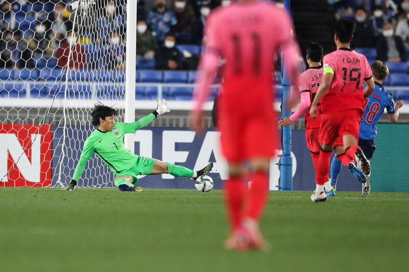 South Korean goalkeeper Lee Seung-kyu (L) blocks a shot by the Japanese side during a football friendly on March 25, 2021, in Yokohama, Japan. (Photo: Yonhap News)