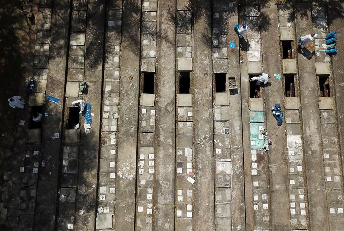 Gravediggers wearing protective suits perform exhumations at Vila Nova Cachoeirinha cemetery amid the COVID-19 outbreak in Sao Paulo, Brazil, on April 1, 2021. (Photo: Reuters-Yonhap News)
