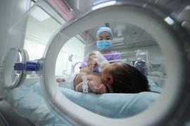A nurse at a hospital in southwestern China feeds a baby on May 11, 2021. (Photo: AFP-Yonhap News)