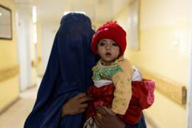 A mother wearing a burqa walks with a baby at the malnutrition ward at the Indra Gandhi hospital in Kabul, Afghanistan October 23, 2021. - Reuters